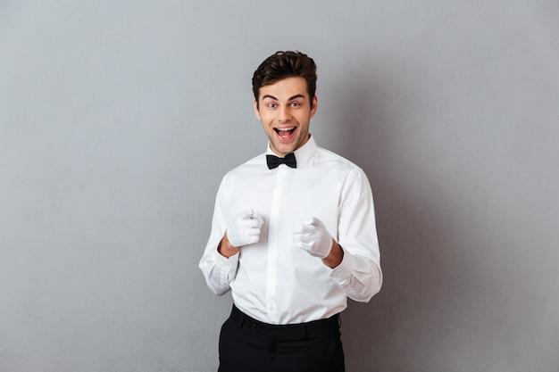 Portret van een vrolijke jonge mannelijke ober