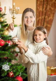 Portret van een vrolijke jonge moeder die de kerstboom versiert met dochter thuis
