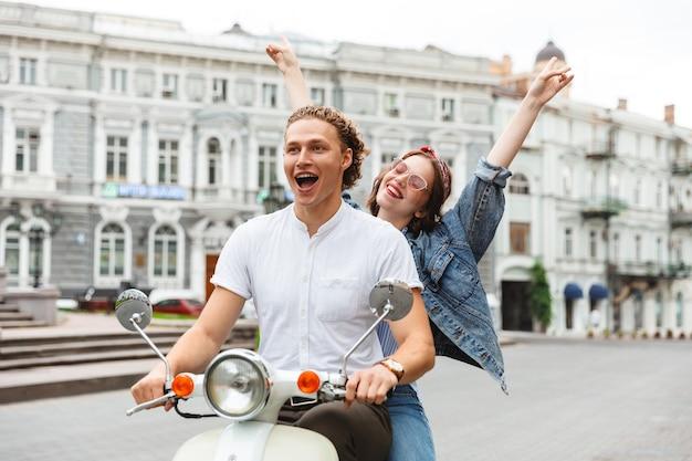 Portret van een vrolijke jonge paar rijden op een motor samen in de stad straat Premium Foto