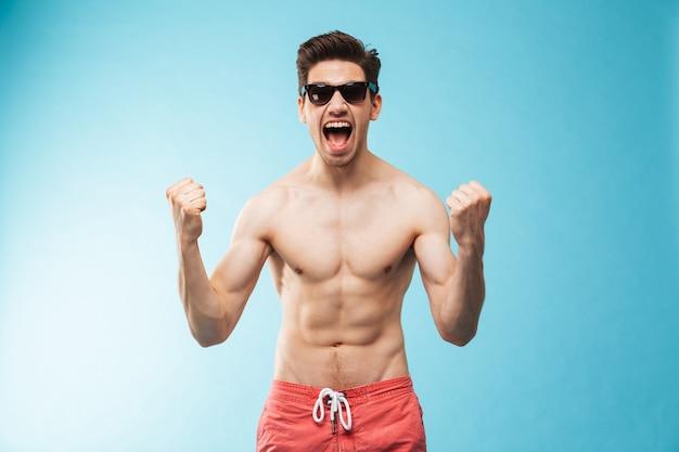 Portret van een vrolijke jonge shirtless man in zwembroek