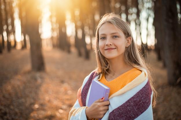 Portret van een vrolijke jonge studente met een boek in haar handen in het herfstpark