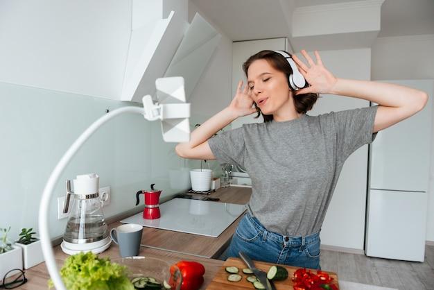 Portret van een vrolijke jonge vrouw die aan muziek luistert