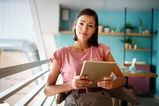 Portret van een vrolijke jonge vrouw die een draagbare pc gebruikt om te bloggen op sociale netwerken