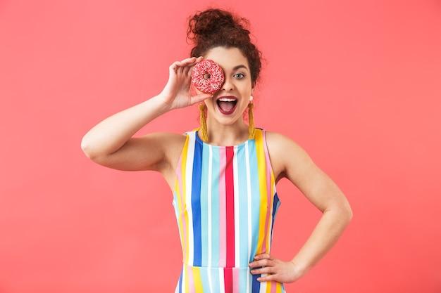 Portret van een vrolijke jonge vrouw die een jurk draagt die geïsoleerd staat over rode achtergrond,