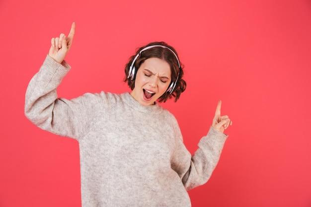 Portret van een vrolijke jonge vrouw geïsoleerd over roze, luisteren naar muziek met een koptelefoon, dansen