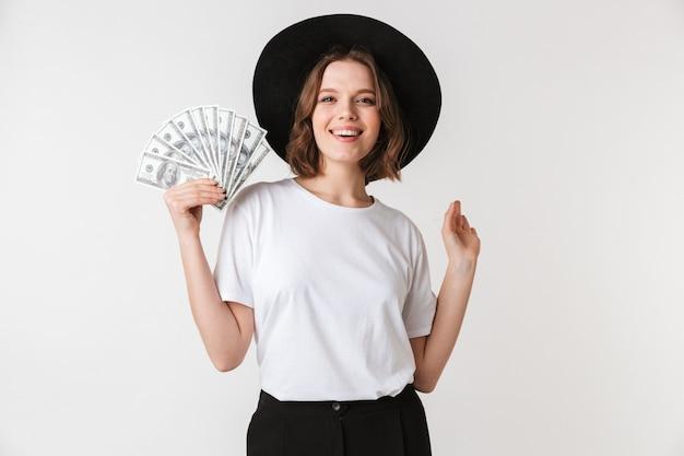 Portret van een vrolijke jonge vrouw gekleed in zwarte hoed