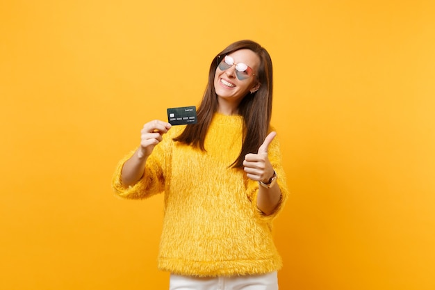 Portret van een vrolijke jonge vrouw in een bonttrui, een hartbril die duim toont met een creditcard die op een felgele achtergrond wordt geïsoleerd. mensen oprechte emoties, lifestyle concept. reclame gebied.
