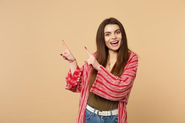 Portret van een vrolijke jonge vrouw in vrijetijdskleding die naar een camera kijkt die wijsvingers opzij richt geïsoleerd op een pastelbeige muurachtergrond. mensen oprechte emoties, lifestyle concept. bespotten kopie ruimte.