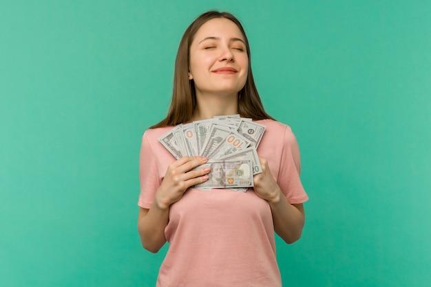 Portret van een vrolijke jonge vrouw met geld bankbiljetten en vieren geïsoleerd op blauwe achtergrond