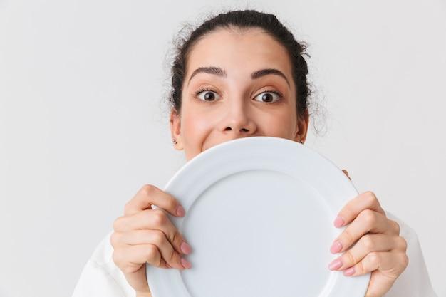 Portret van een vrolijke jonge vrouw met gerechten close-up