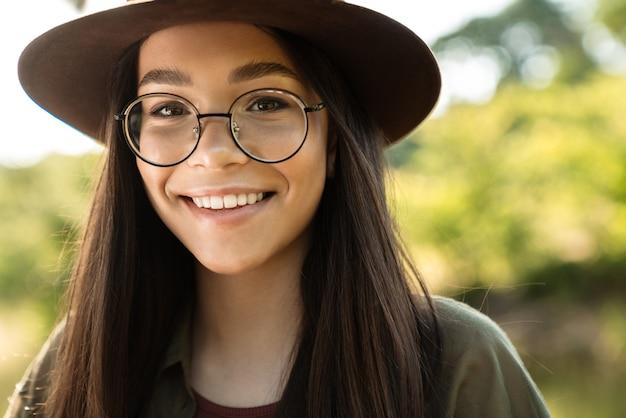 Portret van een vrolijke jonge vrouw met lang donker haar met een stijlvolle hoed en bril die op zonnige dag in een groen park loopt