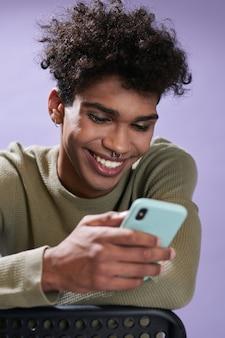 Portret van een vrolijke jongeman die berichten over de telefoon en een glimlachende transgender afro-amerikaanse man