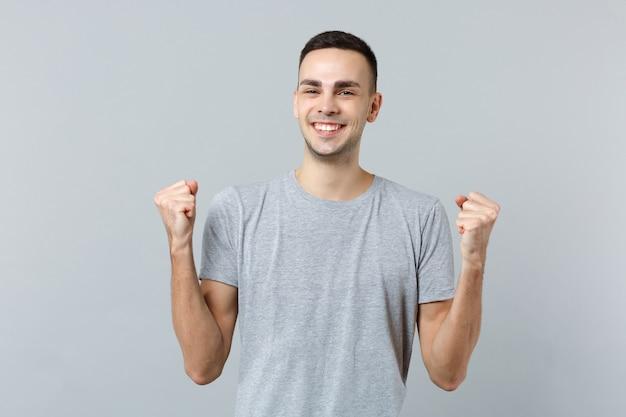 Portret van een vrolijke jongeman in vrijetijdskleding, vuisten gebald als winnaar