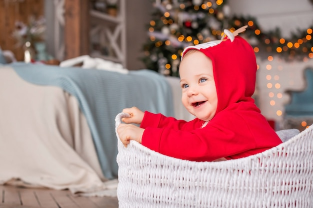 Portret van een vrolijke kleine kinderen in een rood rendierkostuum van de kerstman die in de mand zit tegen de achtergrond van de kerstboom