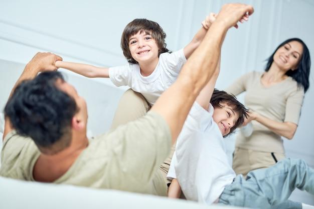 Portret van een vrolijke kleine latijnse jongen die plezier heeft, speelt met zijn ouders en broer of zus, die thuis samen op een bed ligt. gelukkige jeugd, ouderschapsconcept