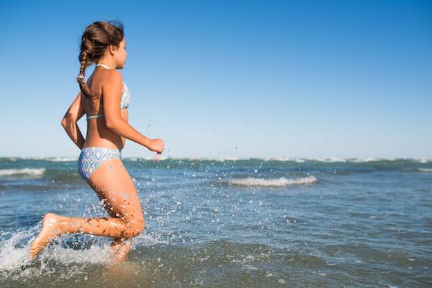 Portret van een vrolijke kleine positieve meisje zwemmen in de zee op een zonnige warme zomerdag