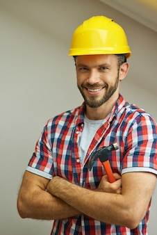 Portret van een vrolijke klusjesman met een helm die lacht naar de camera die staat met gekruiste armen en