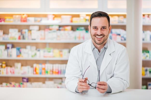 Portret van een vrolijke knappe apotheker die op teller bij drogisterij leunt.
