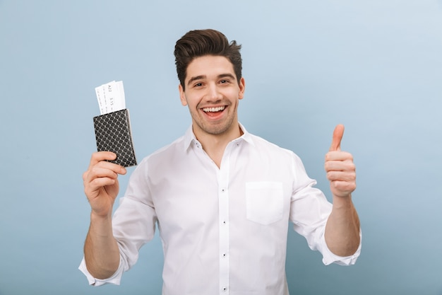 Portret van een vrolijke knappe jongeman die geïsoleerd op blauw, paspoort met vliegtickets vasthoudt