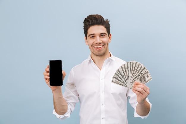 Portret van een vrolijke knappe jongeman die geïsoleerd op blauw staat, geldbankbiljetten toont, een lege scherm mobiele telefoon toont