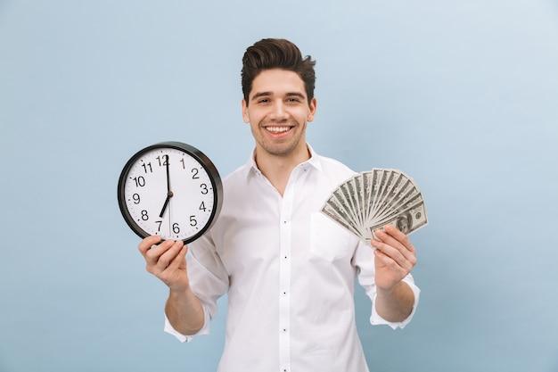 Portret van een vrolijke knappe jongeman die geïsoleerd op blauw staat, geldbankbiljetten toont, wekker toont