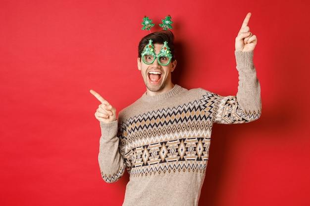 Portret van een vrolijke knappe man in feestbril en kersttrui, dansend en wijzende vingers zijwaarts, genietend van nieuwjaarsviering, staande op rode achtergrond.