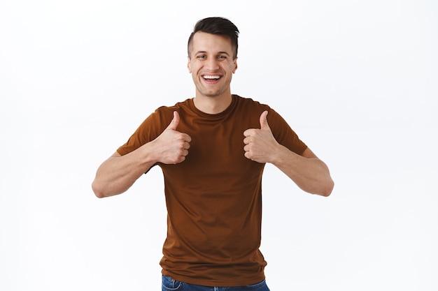 Portret van een vrolijke, knappe tevreden blanke man die positieve feedback geeft, product aanbevelen