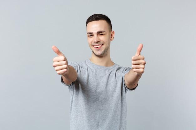 Portret van een vrolijke, knipperende jonge man in vrijetijdskleding die staat en duimen laat zien