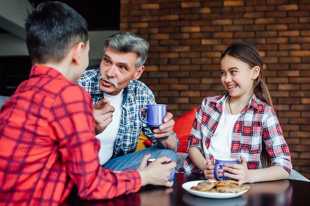 Portret van een vrolijke lachende oudere man die thee drinkt met een koekje terwijl hij geniet van de tijd met zijn kleinkinderen.