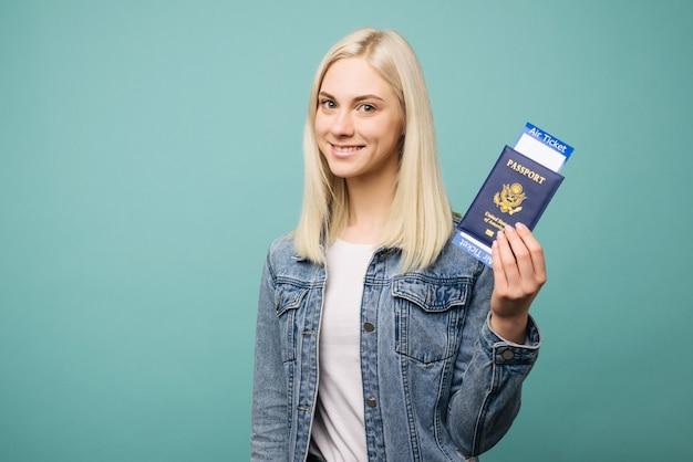 Portret van een vrolijke leuke amerikaanse meisjesreiziger die paspoort met kaartjes toont die over blauwe achtergrond worden geïsoleerd