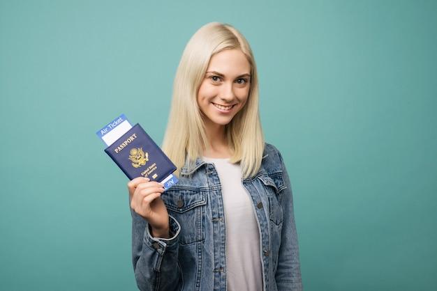 Portret van een vrolijke leuke amerikaanse meisjesreiziger die paspoort met kaartjes toont
