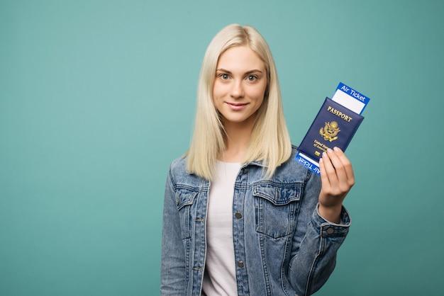 Portret van een vrolijke leuke meisjesreiziger die paspoort met kaartjes toont