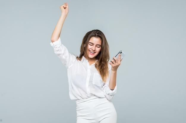 Portret van een vrolijke leuke vrouw luisteren muziek in koptelefoon en dansen op een witte achtergrond