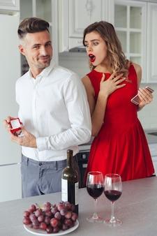 Portret van een vrolijke man die zijn geschokte vriendin voorstelt