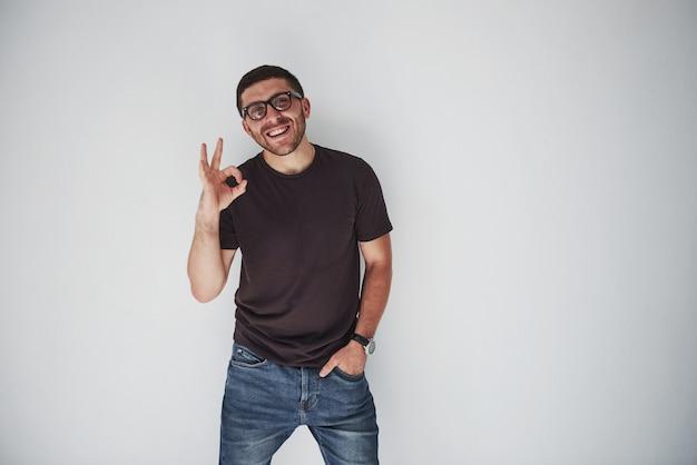 Portret van een vrolijke man in t-shirt en bril en ok teken weergegeven: