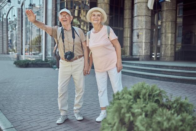 Portret van een vrolijke man met een digitale camera en zijn vrouw die een taxi aanhoudt