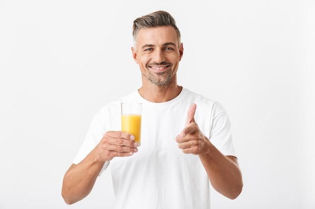 Portret van een vrolijke man van de jaren '30 met borstelharen die een casual t-shirt draagt met een glas sinaasappelsap op wit wordt geïsoleerd