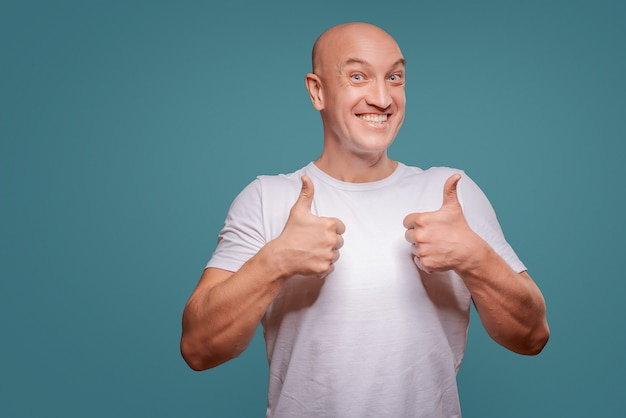 Portret van een vrolijke mens die ok gebaar toont dat op de blauwe achtergrond wordt geïsoleerd