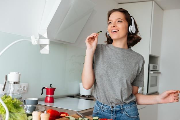 Portret van een vrolijke mooie vrouw die aan muziek luistert