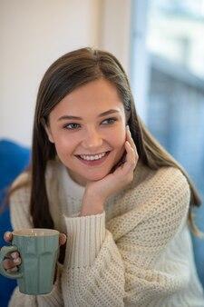 Portret van een vrolijke mooie vrouw die lacht zittend met een kopje thee