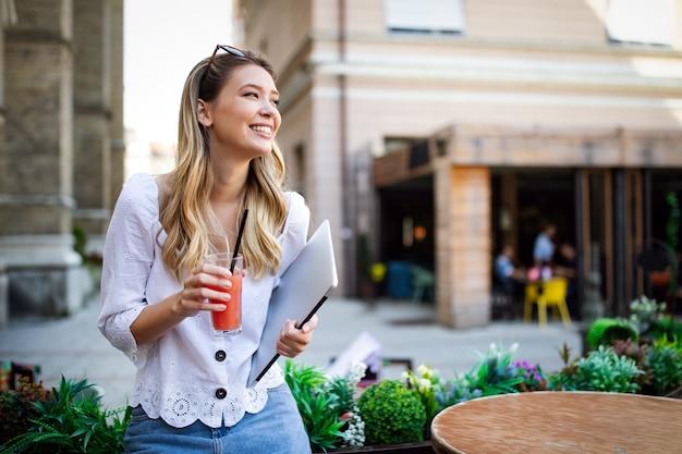 Portret van een vrolijke mooie vrouw die werkt, studeert op een laptop