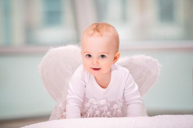 Portret van een vrolijke ondeugende baby met witte engelenvleugels die naar de kijker kruipen