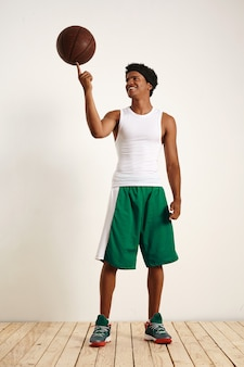 Portret van een vrolijke ontspannen aantrekkelijke man in witte en groene basketbaluitrusting die een vintage leerbasketbal op zijn wijsvinger in evenwicht houdt