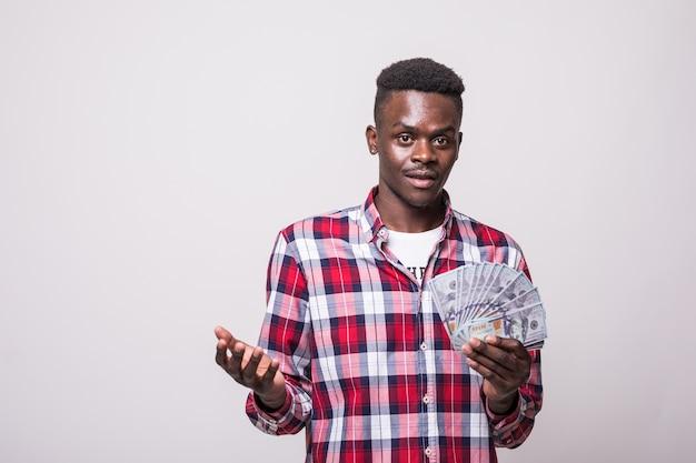 Portret van een vrolijke opgewonden afro-amerikaanse man die geldbankbiljetten houdt en geïsoleerd kijkt