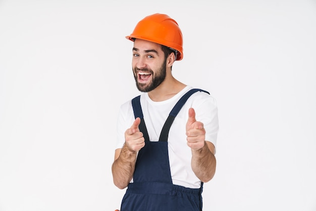 Portret van een vrolijke optimistische jonge man bouwer in helm poseren geïsoleerd over witte muur wijzend naar jou.