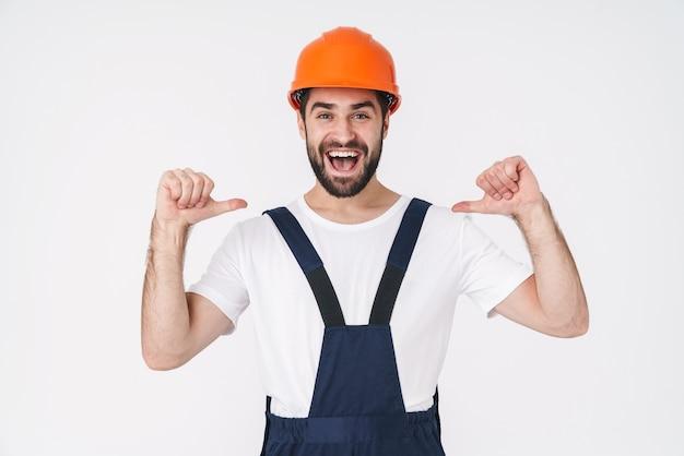Portret van een vrolijke optimistische jonge man bouwer in helm poseren geïsoleerd over witte muur wijzend naar zichzelf.