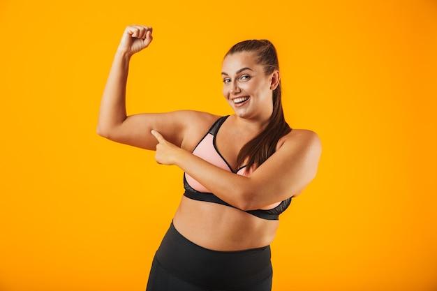 Portret van een vrolijke overgewicht fitness vrouw, gekleed in sportkleding staande geïsoleerd over gele muur, biceps buigen