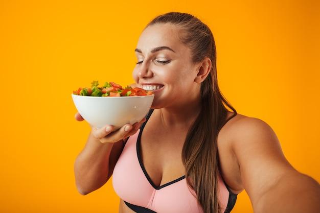 Portret van een vrolijke overgewicht fitness vrouw, gekleed in sportkleding staande geïsoleerd over gele muur, een selfie met mobiele telefoon nemen, kom met salade tonen