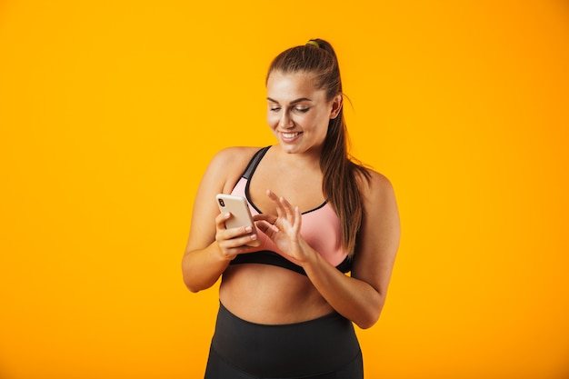 Portret van een vrolijke overgewicht fitness vrouw, gekleed in sportkleding staande geïsoleerd over gele muur, met mobiele telefoon