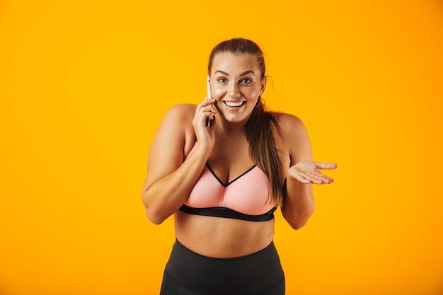 Portret van een vrolijke overgewicht fitness vrouw, gekleed in sportkleding staande geïsoleerd over gele muur, praten over de mobiele telefoon
